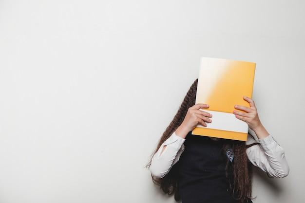 Девушка, закрывающая лицо записной книжкой