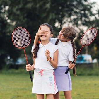 Girl covering her friend eyes holding badminton