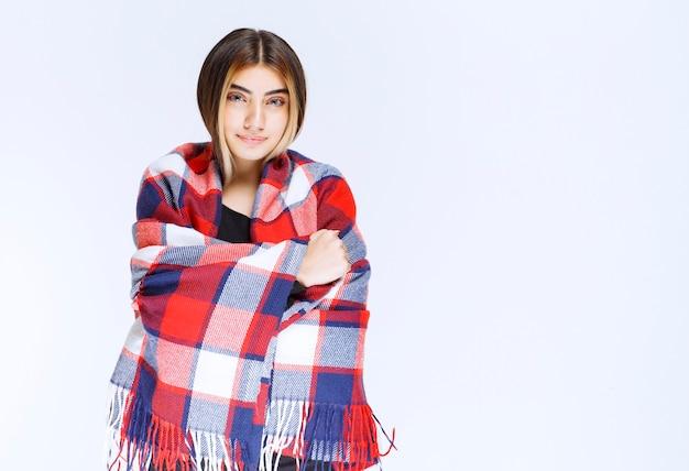 寒さを感じながら赤青の毛布で身を包んだ少女。