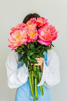 女の子はピンクの牡丹の美しい花束、お誕生日おめでとうまたはバレンタインデーで彼女の顔を覆います