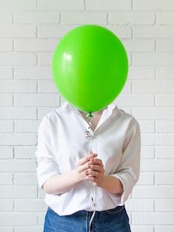 Девушка закрывает лицо зеленым шаром. понятие безличности.