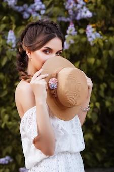 소녀는 밀짚 모자로 그녀의 얼굴을 다룹니다. 여름 메이크업. 큰 초상화. 배경을 흐리게, 개념