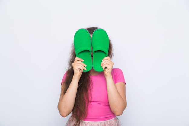 Girl covers her face with slippers on white background