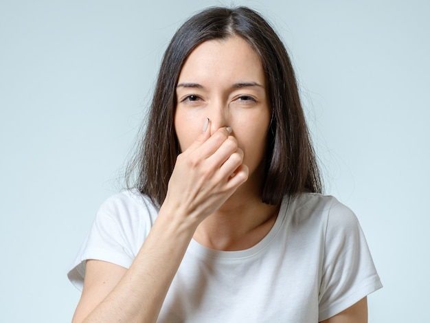 Girl covers nose with hand showing that something stinks