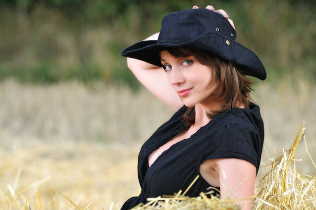 Girl in cowboy hat sits on haystack