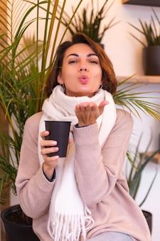 Una ragazza in un accogliente bar si riscalda con una tazza di caffè caldo