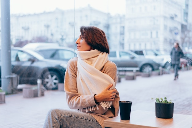 A girl in a cozy cafe warms herself up with a cup of hot coffee