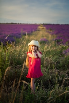 A girl in a crimson dress in a field with purple flowers,