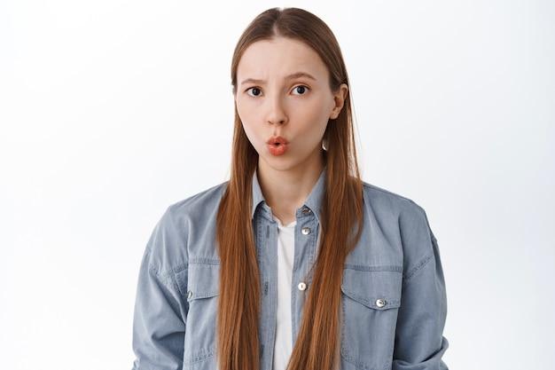 소녀는 고통스럽고 입술을 오므리고 불쾌하고 불쾌한 것을 응시하는 것처럼 인상을 찌푸리고 흰 벽 위에 서 있는 무언가에서 움츠러듭니다.