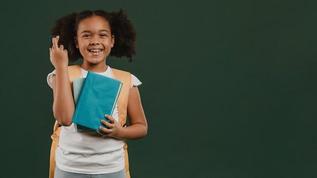 指を交差させて本を持っている女の子