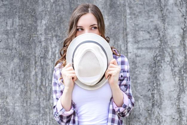 Girl curly hair holding headwear near face grey wall background