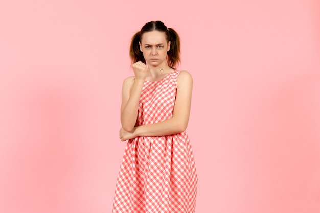 Girl in cute bright dress with angry expression on pink