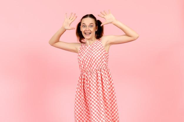 Ragazza in abito luminoso carino con espressione eccitata sul rosa