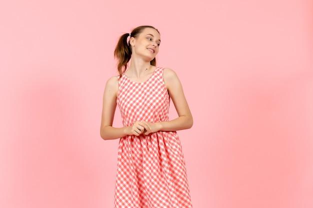 Ragazza in abito luminoso carino con espressione sorridente sul rosa