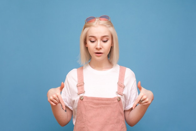 Girl in cute clothes shows her fingers down and looks at an empty space, isolated on blue.