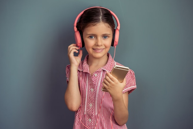 Girl in cute dress and headphones is listening to music.