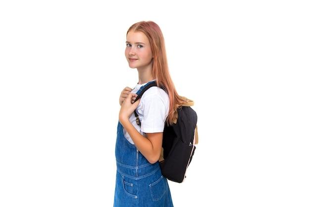 소녀 귀여운 십 11 세 여학생 배낭과 흰색 배경에 미소와 함께 카메라를 찾고. 데님 드레스를 입고 복사 공간