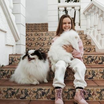 Ragazza e simpatici cuccioli bianchi seduti sulle scale