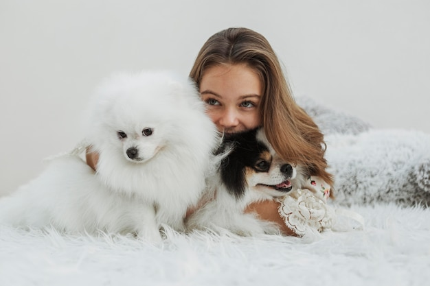 Girl and cute white pups sitting on the bed