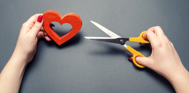 Girl cuts the red heart with scissors. the concept of breaking relations, quarrels and divorce.