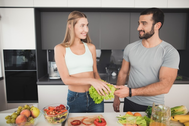 Girl cuts vegetables for a salad and a man helps her