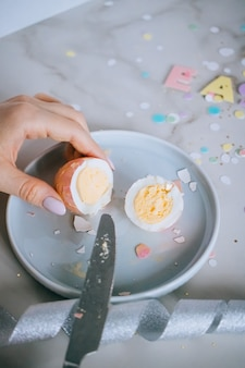 Girl cutting golden easter eggs on marble background, confetti, sparkles, ribbons.