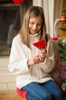 クリスマスの装飾のために紙の雪片を切る女の子