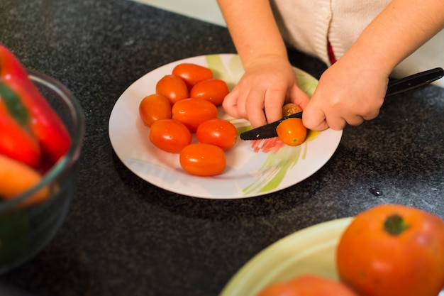 Girl cutting tomatoes on plate over the kitchen worktop