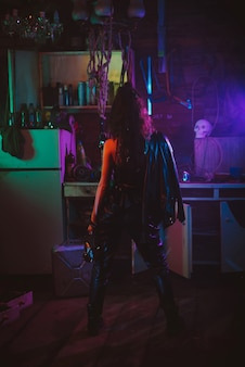 Girl in a cyberpunk suit with a neon light in the garage. steampunk cosplay in the post-apocalyptic style of the future