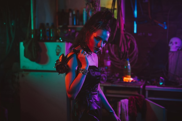 Girl in a cyberpunk suit with a neon light in the garage. steampunk cosplay in the post-apocalyptic style
