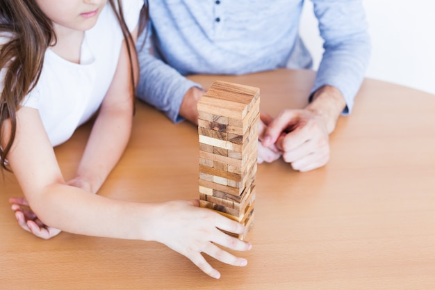 Girl and dad play a game at home, cost a tower of blocks, cubes, jenga, puzzle for brain development, mental intelligence.