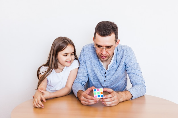 Girl and dad play a game at home, rubik's cube, puzzle for brain development, mental intelligence