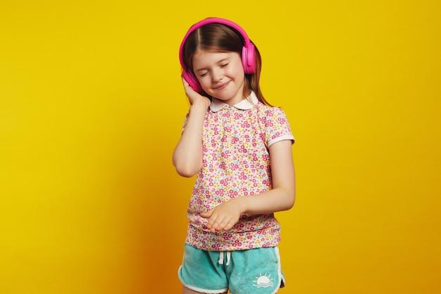 Девушка танцует и слушает музыку в наушниках, с удовольствием закрывает глаза