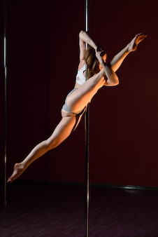 The girl dances near the pole