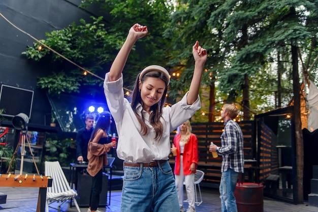 彼女の友人が屋外のお祝いパーティー中に色のランプに照らして踊っている間、前景で踊っている女の子。