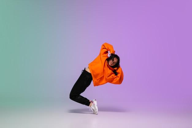 Девушка танцует хип-хоп в стильной одежде на градиентный фон в танцевальном зале в неоновом свете.