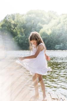 강 부두에서 젖은 드레스를 입고 춤추는 소녀. 하이라이트가 있는 사진