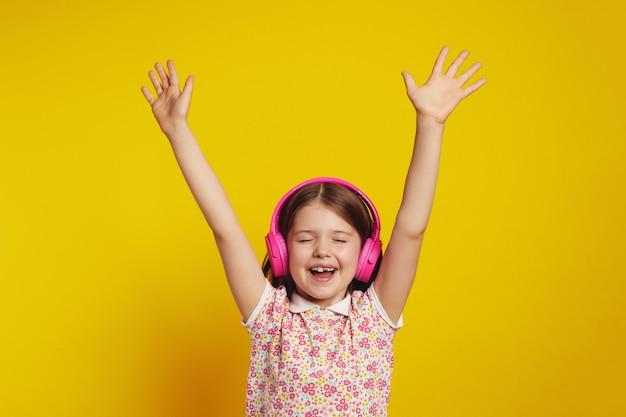 Девушка танцует в беспроводных наушниках с закрытыми глазами держит руки поднятыми