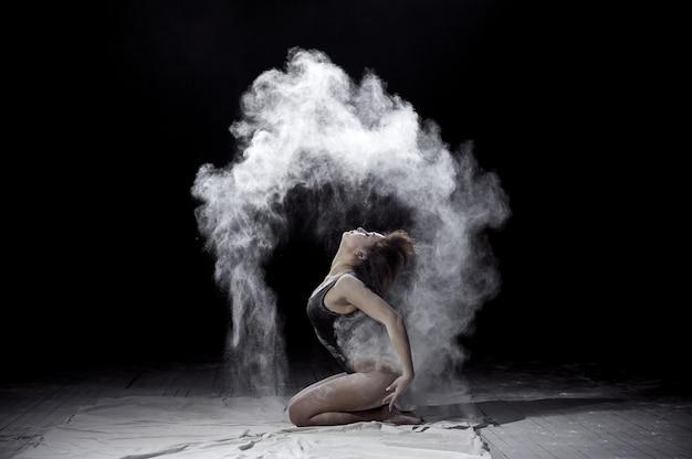 Девушка танцует с мукой на черном фоне на сцене