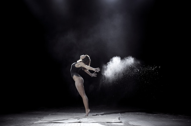 Girl dancing with a flour on black