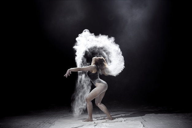 Girl dancing with a flour on black.