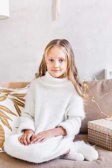 Girl, daughter, baby sitting on the sofa in a light warm sweater, long blonde hair, european appearance and light interior