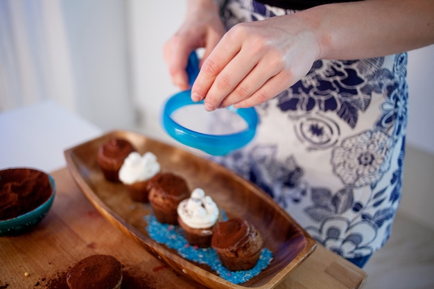 Girl decorates cupcakes, holding plate, muffins and plate of ingredients for decoration on the table