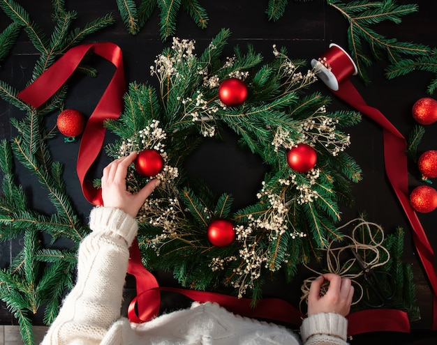 Девушка сама украшает рождественский венок на столе дома