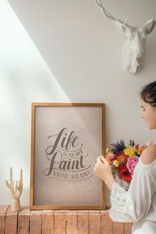 Девушка украшает стену мотивационной рамкой