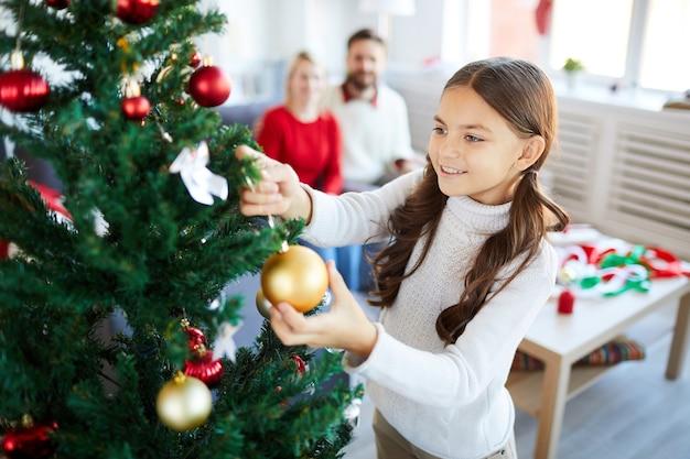 Ragazza che decora l'albero di natale