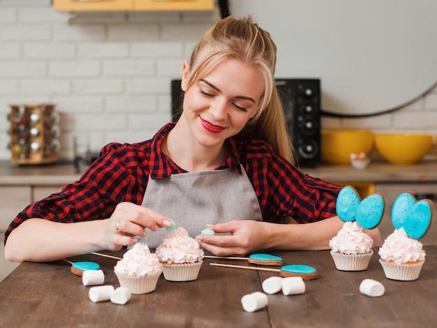 キッチンの木製テーブルで白いクリームと青いケーキポップでカップケーキを飾る女の子
