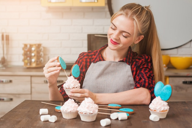 Girl decorating cup cakes with white cream and blue cake-pops at kitchen wooden table