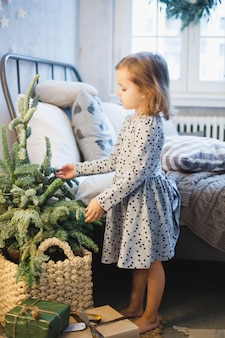 Girl decorating the house with christmas tree and christmas decor.