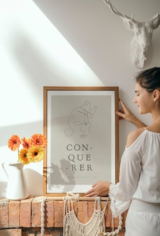 Girl decorating a wall with a conqueror frame